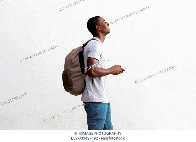 Side portrait of a traveling african american man holding cell phone
