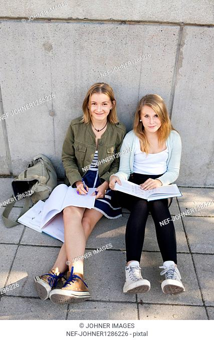 Two teenage girls sitting on pavement