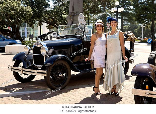 Art deco design: Two women in dresses from the twenties posing in front of a Ford Model A antique car, Napier, Hawke's Bay, Nort