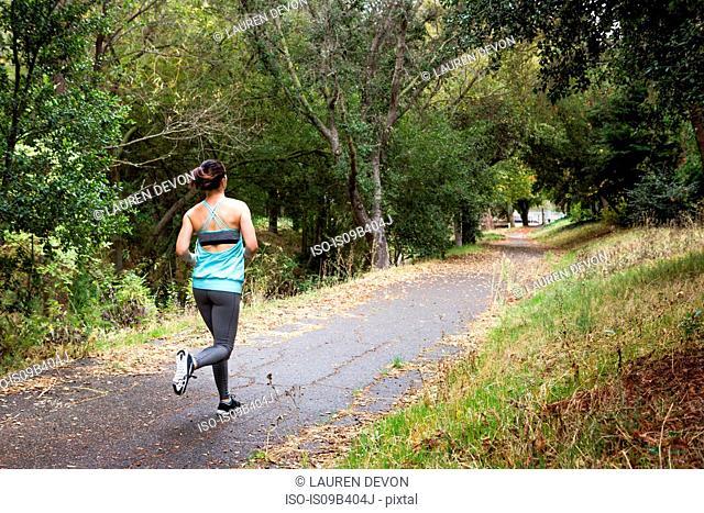 Rear view of female runner running in park