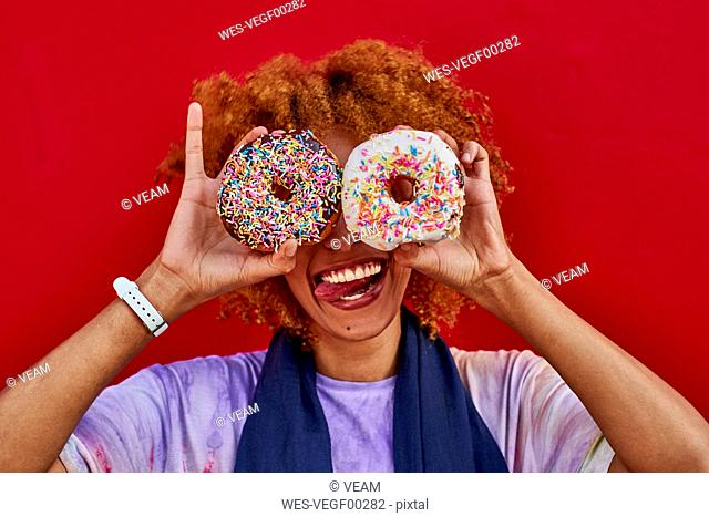 Playful woman holding two donuts in front of her eyes
