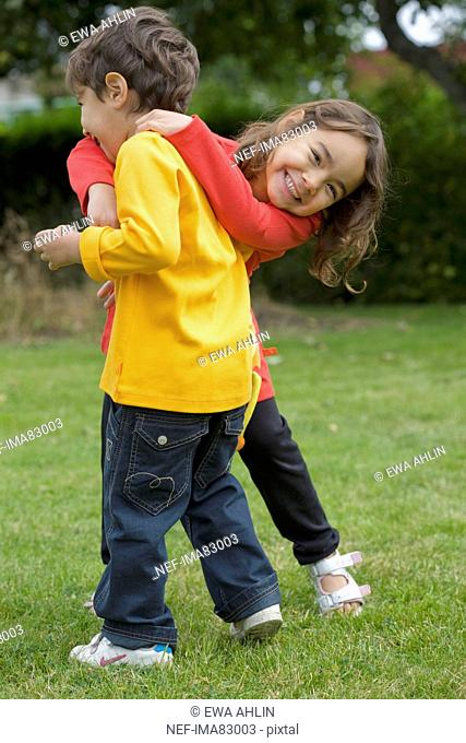 Boy and girl playing on grass
