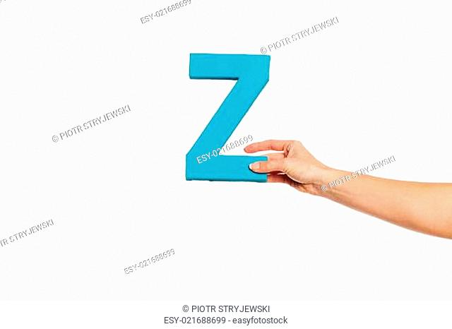 hand holding up the letter Z from the right
