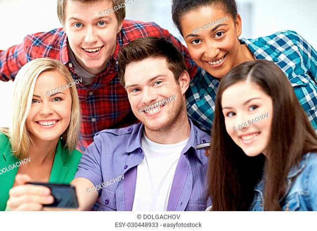 education, people, friendship, technology and learning concept - group of happy international high school students or classmates with smartphone taking selfie...