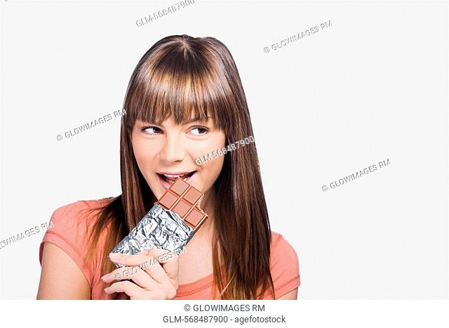 Close-up of a young woman eating a chocolate