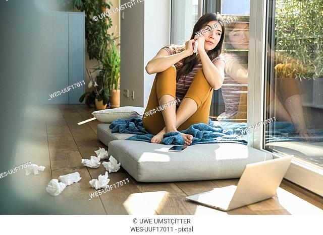 Thoughtful young woman sitting at the window at home with laptop and tissues