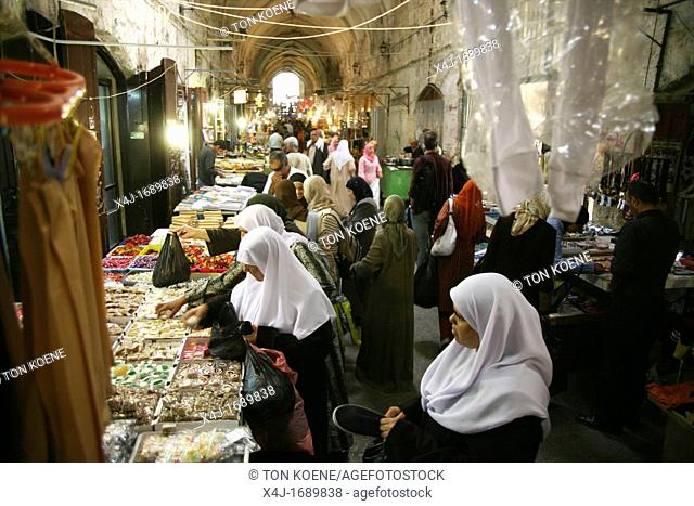 Women buy sweets at a market in the old city section of Jerusalem