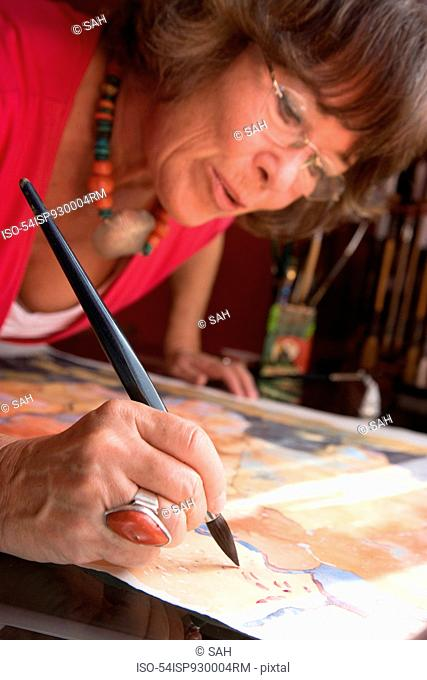 Older woman painting with watercolors
