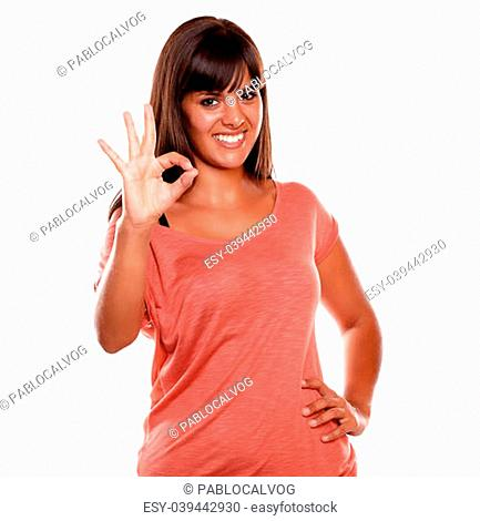 Charming young woman showing you ok sign on isolated background