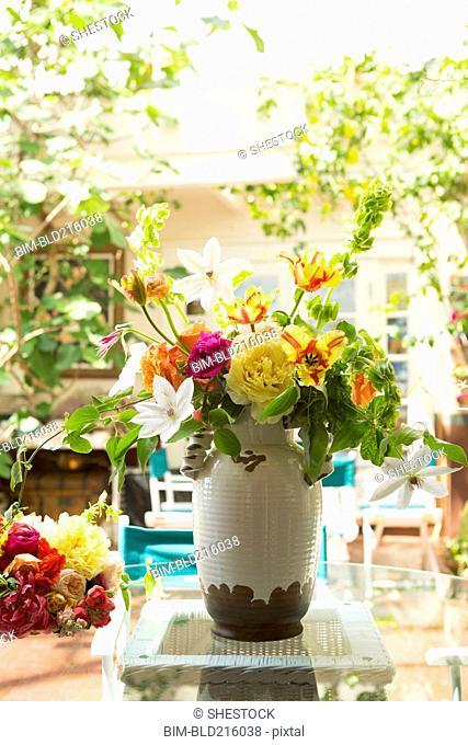 Bouquet of flowers in vase on backyard patio