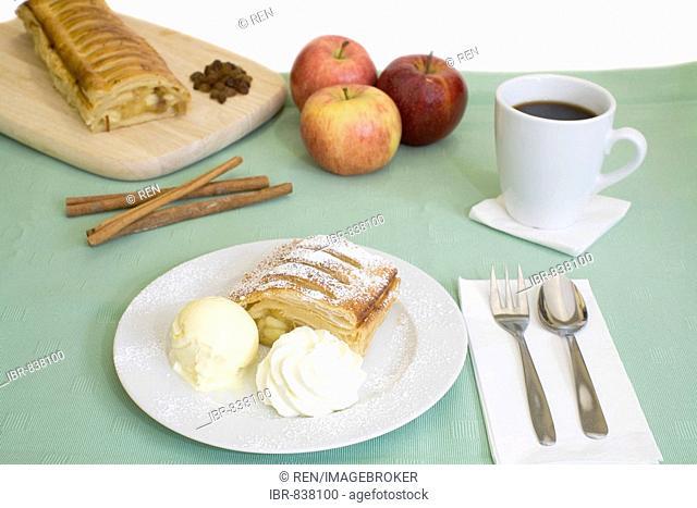 Apple strudel with vanilla ice cream and cream, a cup of coffee, apples, cinnamon sticks and raisins