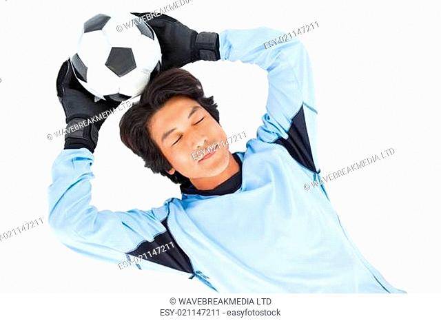 Goalkeeper in blue holding ball