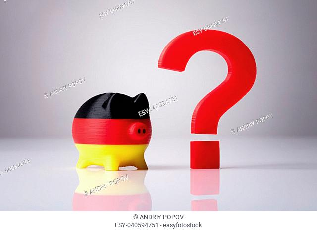 Close-up Of Piggybank Painted With German Flag And Red Question Mark Sign On Reflective Background