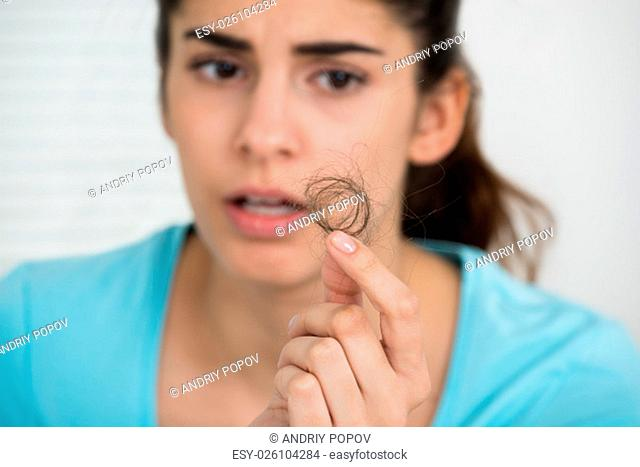 Shocked young woman looking at hair loss