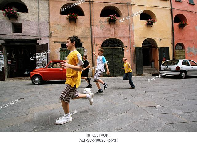 Boys Running With Soccer Ball In Street