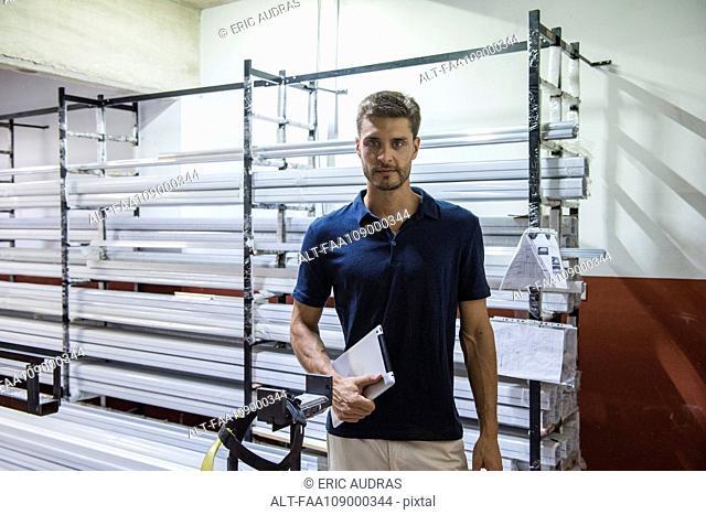 Man in factory warehouse, portrait