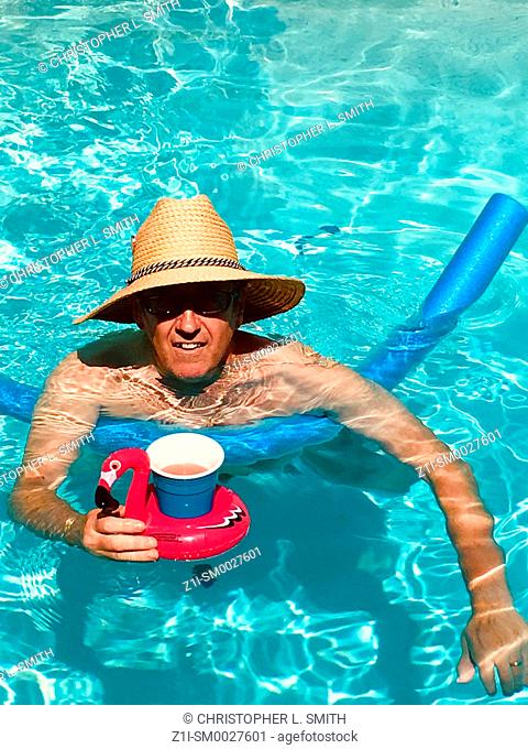 Man enjoying pool time wearing a sun hat with a floating drinks holder containing a fruit punch drink
