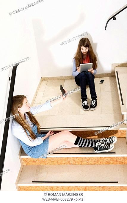 Two teenage girls sitting on stairs using smartphone and digital tablet