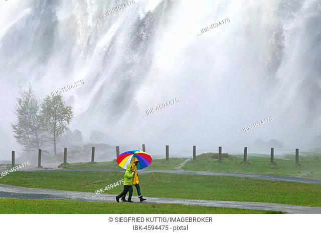 Strollers with colourful umbrella in front of waterfall, Powerscourt waterfall, Enniskerry, County Wicklow, Ireland
