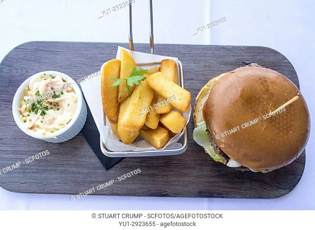 Burger, fries in a basket and coleslaw served on a black slate