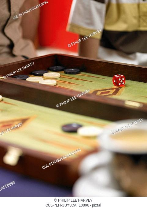 Family playing backgammon, focus on board and dice, close-up
