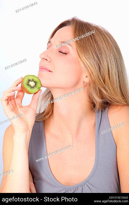 Beautiful blond woman eating kiwis