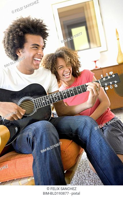 Woman laughing while boyfriend plays guitar