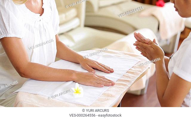 A professional beauty therapist giving a gentle hand and arm massage to a customer