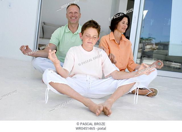 Boy and his parents meditating in the lotus position