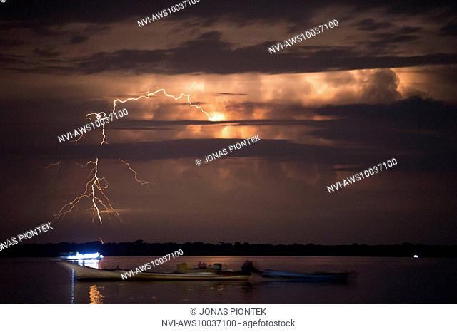 Distant positive cloud-to-ground discharges behind fisher boats on lake Maracaibo (Catatumbo thunderstorm, the place with the highest lightning density...
