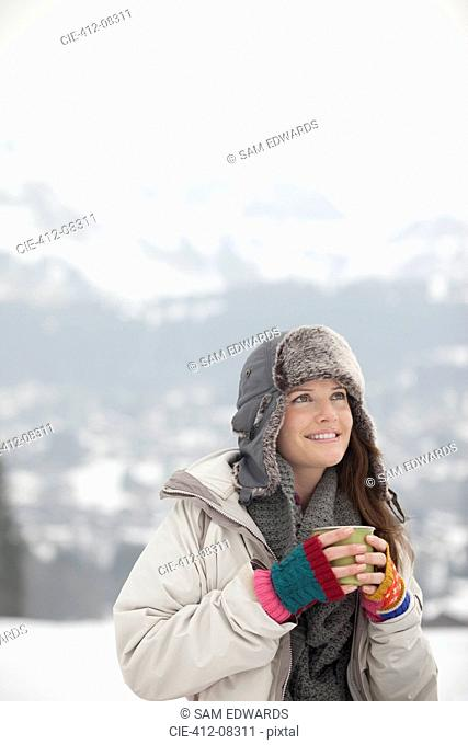 Smiling woman drinking coffee in snowy field