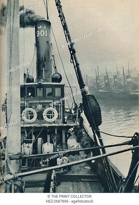 'Entering Grimsby Docks at the end of a North Sea voyage is the fishing vessel Saurian', 1937. Artist: Unknown