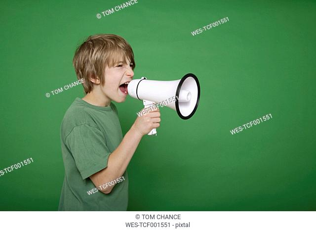 Boy screaming in megaphone against green background
