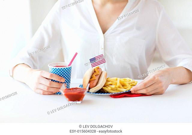 national holidays, celebration, food and patriotism concept - close up of woman eating hot dog and french fries with drink in disposable paper cup at 4th july...