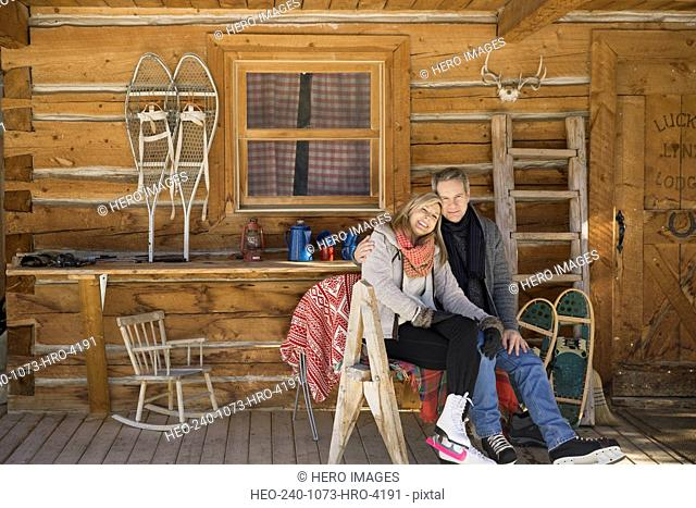 Couple sitting on cabin porch wearing ice skates