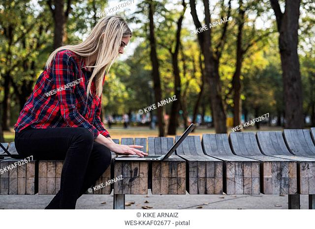 Young woman sitting on bench outdoors working on laptop