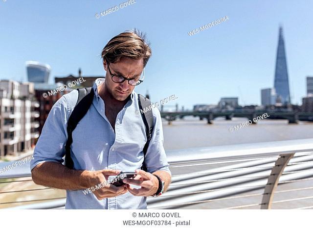 UK, London, man using his smartphone on the Millennium Bridge