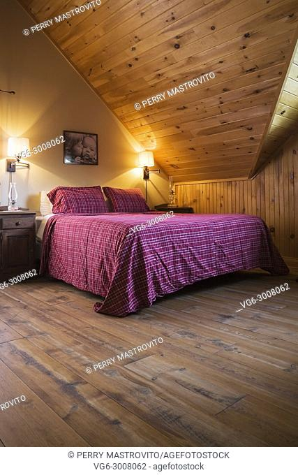 King size bed in master bedroom on the upstairs floor inside a cottage style log home, Quebec, Canada. This image is property released. CUPR0289
