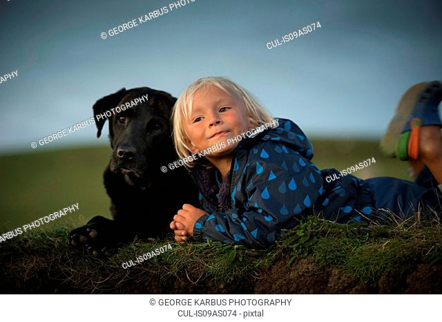 Young boy lying down with dog in field