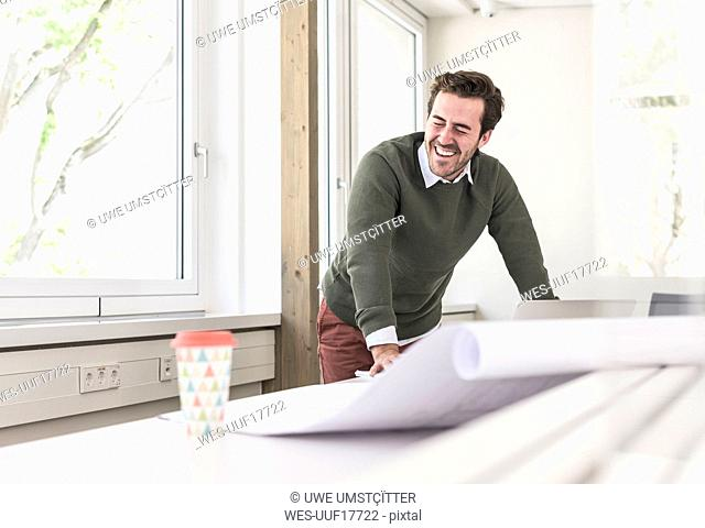 Laughing young architect working on blueprint in bright office