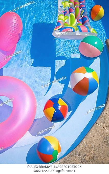 Beach balls and toys in a sparkling blue swimming pool