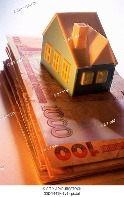 Model of a house on a stack of banknotes
