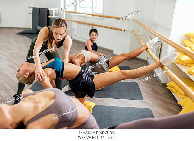 Fitness instructor practicing barre workout with young women in gym