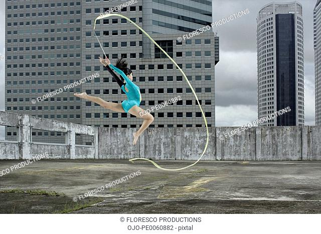 Woman gymnast outdoors on rooftop jumping in air with ribbon