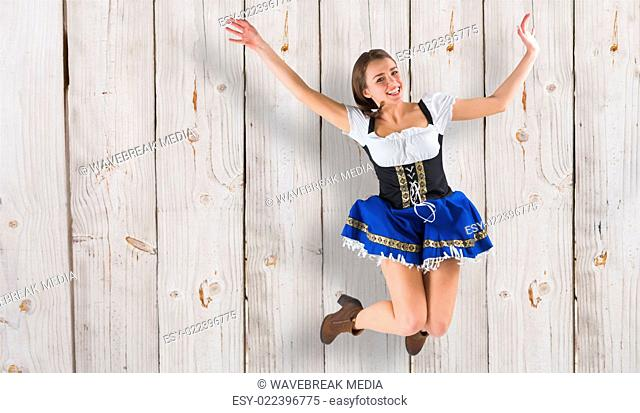 Composite image of pretty oktoberfest girl smiling and jumping