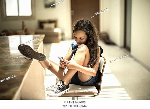A girl sitting looking at a mobile phone screen with feet up on a kitchen counter