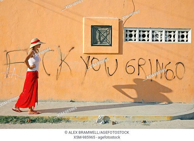 Tourist walking past a bit of anti-American grafitti on a wall in Playa del Carmen, Mexico
