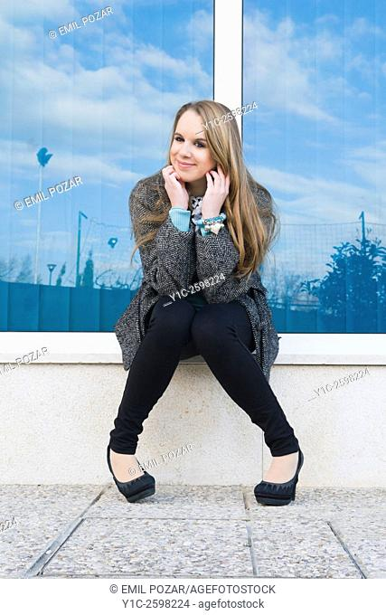 Cute teen-girl sitting and waiting before shiny glass wall
