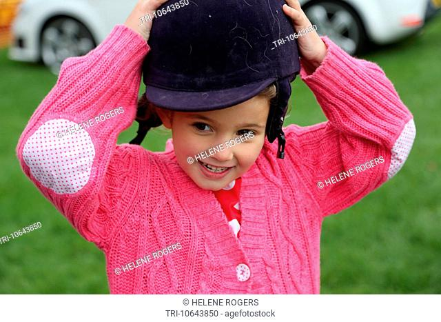 Girl Putting On Horse Riding Helmet At Cheam Village Fair Surrey England