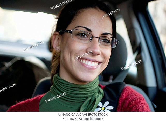 Attractive young woman drives her car